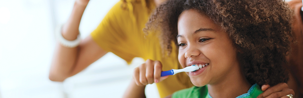 Young girl brushing teeth with mother standing behind her.