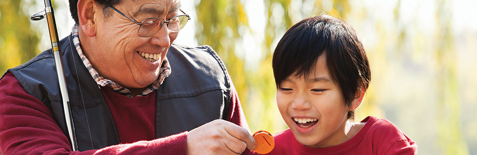 Asian father and son looking at fishing lure.