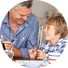 Grandpa and Grandson painting at a kitchen table