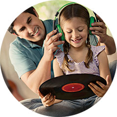 Dad helping his daughter listen to records with headphones