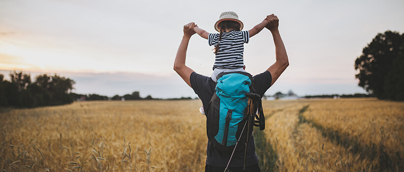 Young child getting a ride on Dad's shoulders.