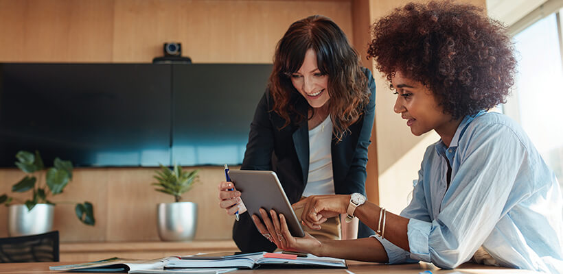 Two women are working together on a tablet in a conference room.